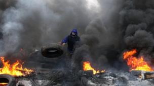 A pro-Russian protester burns tires in preparation for battle with the Berkut (Ukrainian special police forces) on the outskirts of the eastern Ukrainian city of Slavyansk on 13 April 2014