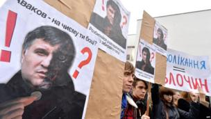 "Protesters hold placards depicting acting Ukrainian Interior Minister Arsen Avakov reading ""Avakov - whose side are you on? Either stop separatists or get out!"" during their protest action at the ministry in Kiev on 14 April 2014"