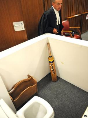 State prosecutor Gerrie Nel, alongside a reconstruction of a toilet cubicle in court on 14 April 2014