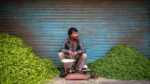 A man waits for customers next to heaps of green chillies