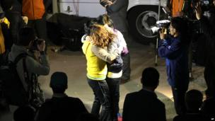 Relatives hug each other as they wait for missing people at a port in Jindo, South Korea - 16 April 2014