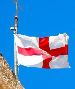 The flag of St George flying against a blue sky