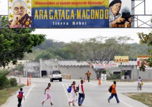 People pass under a billboard reading Welcome to the magical world of Macondo, as they enter Aracataca, Colombia, 4 JAN 2006.