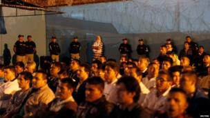 Prison guards and inmates watch other prisoners performing at the Sarita Colonia prison yard in Lima, on April 15, 2014.