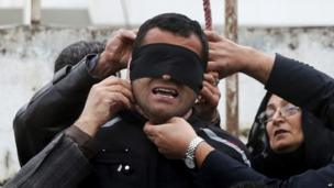 This picture provided by ISNA, a semi-official news agency shows Maryam Hosseinzadeh, right, and her husband Abdolghani, left, removing the noose from the neck of blindfolded Bilal who was convicted of murdering their son Abdollah in the northern city of Nour, Iran (17 April 2014)