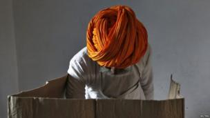 A man wearing a traditional turban casts his vote inside a polling station in Ajmer district in the desert Indian state of Rajasthan (17 April 2014)