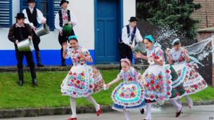 Local school girls in traditional clothes run away as boys throw buckets of water in Kalocsa (17 April 2014