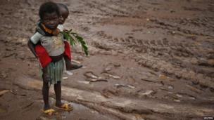 Two children, one holding leaves, stand in the mud in Boda, CAR - Monday 14 April 2014