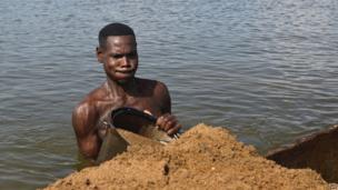 A man tipping sand into a boat, Bangui, CAR - Saturday 12 April 2014