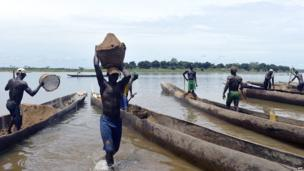Men tipping sand into a boat, Bangui, CAR - Saturday 12 April 2014