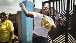 An ANC supporter throwing water bottles, Soweto, South Africa - 12 April