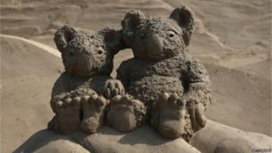 Two koala bears sculpted out of sand