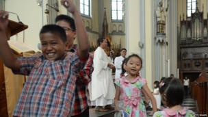 While these children sing and dance during a mass in Indonesia.
