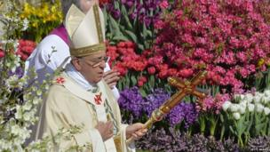 And in Rome, the leader of the Catholic Church Pope Francis walks past flowers as he arrives at St Peter's square to give the traditional Easter mass.