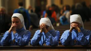 Three nuns pray after the conclusion of Easter Mass at the Cathedral of the Holy Cross in Boston, Massachusetts, 20 April 2014