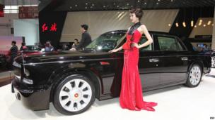 Models pose with a Hongqi L5 car on display at the Beijing Auto Show