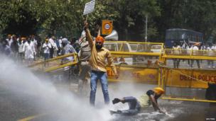 Police use a water cannon to disperse Sikh protesters during a demonstration in front of India's ruling Congress party headquarters in New Delhi