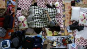 Family members of a missing passenger onboard the South Korean ferry Sewol, which capsized on Wednesday, rest as they wait for news
