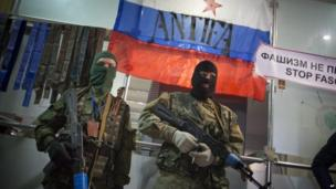 Masked pro-Russian gunmen guard an entrance of the Ukrainian regional office of the Security Service with a Russian National flag is in background in Luhansk, Ukraine