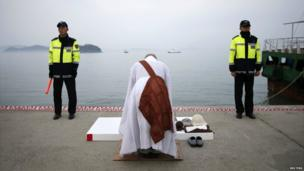 Two policemen stand guard as a priest says prayers at the port in Jindo - 22 April 2014