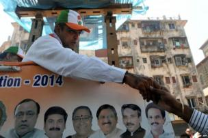 Indian Congress party candidate Milind Deora (L) greets a supporter during an election roadshow in Mumbai on April 12, 2014