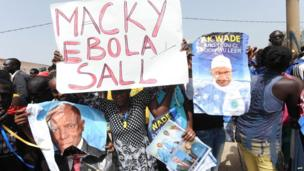 "Supporters of Senegal's former president holding up a sign reading: ""Macky Ebola Sall"", Dakar, Senegal - Wednesday 23 April 2014"