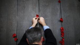 A man places a poppy flower into the World War I Wall of Remembrance on ANZAC Day at the Australian National War Memorial in Canberra on 25 April, 2014