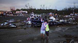 Lori Berseth (R) is consoled after searching for her missing Black Labrador dog after a tornado destroyed the town of Mayflower on 17 April