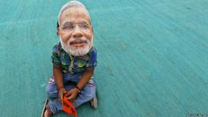 A young boy wearing a mask of BJP prime ministerial candidate Narendra Modi waits for the start of an election rally in a town in Gujarat - 28 April 2014
