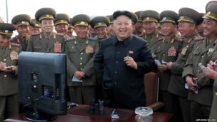 North Korean leader Kim Jong Un laughs with a group of senior figures in the armed forces during a visit to a military installation - distributed on 27 April 2014.