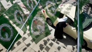 A woman hails a taxi while standing under Patriotic Union of Kurdistan (PUK) party flags