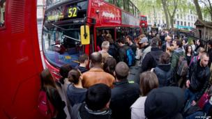 Commuters jostle for access to buses near Victoria station in London