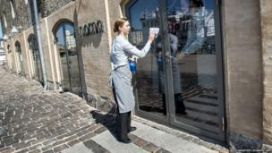 A staff member cleans a window outside Noma restaurant in Copenhagen