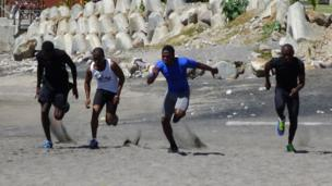 Four men running on sand.