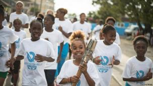 A group of children running together. A young girl holds the Queen's Baton.