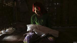 Gorima Khatu holds the covered body of her three-month-old daughter Asoma Khatu, who just died of fever and diarrhoea, in their room at the Kyein Ni Pyin camp for internally displaced people in Pauk Taw, Rakhine state (April 2014)