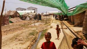 Rohingya children walk past shelters inside the Kyein Ni Pyin camp for internally displaced people in Pauk Taw, Rakhine state (April 2014)