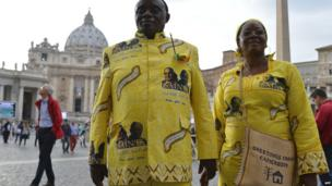 A couple from Cameroon wearing clothes with the pictures of late Pope John Paul II and John XXIII in St Peter's square, the Vatican, Saturday 26 April 2014