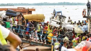 People loaded down with their belongings get off a boat in Kinshasa, DR Congo - Tuesday 29 April 2014
