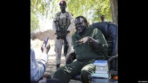 Riek Machar talking as he sits in a chair under a tree in South Sudan - Tuesday 29 April 2014