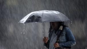 A pedestrian crosses the street in a rainstorm, Wednesday, April 30, 2014, in Philadelphia.