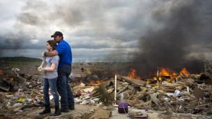 Michael Stanek hugs his daughter Kennedy Stanek as they take a break from helping friends sift though the rubble of their homes in Vilonia, Arkansas 30 April 2014