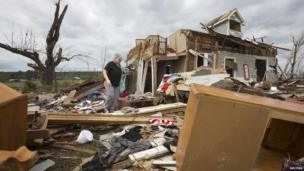 Patsy Reno, mother of Dawn Loving, searches through the rubble of her home for mementos in Vilonia, Arkansas 30 April 2014