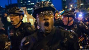 """Police yell """"get back"""" to crowds of people during an anti-capitalist demonstration in Seattle, Washington"""