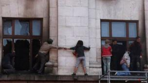 People try to escape from the upper storey of the burning building in Odessa - 2 May 2014