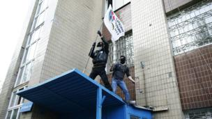 Pro-Russia protesters wave a Donbass flag from the military prosecutor's office building in Donetsk - 4 May 2014