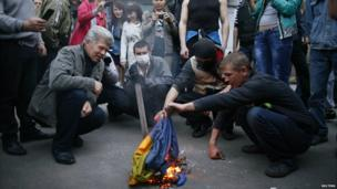 Pro-Russia protesters burn a Ukrainian flag in Donetsk - 4 May 2014