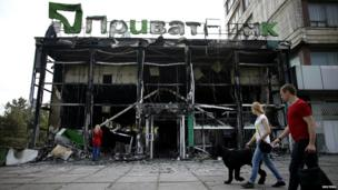 People walk past a gutted branch of Privat Bank near the town hall in Mariupol eastern Ukraine - 4 May 2014