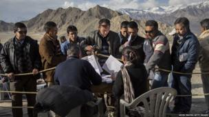 Indian election workers check voting machines before leaving a central collection point for polling stations in Leh, Ladakh