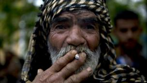 A Palestinian man smokes a cigarette as he takes part in a demonstration in Gaza City - 8 May 2014